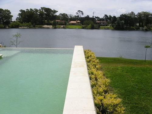 estilo contemporáneo. jardín con piscina y fondo al lago.